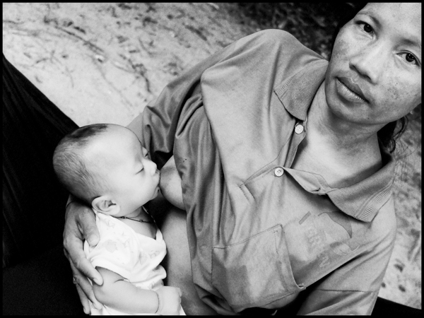 A young mother breastfeeding her baby while on a job cleaning Preah Khan temple side siem reap, june 2014