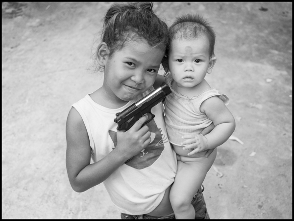 Playing games with a plastic gun at the slums just outside Siem Reap siem reap, october 2014