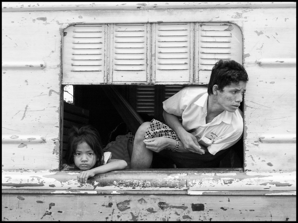 A father is looking out of the window of the train that would take him and his daughter to Battambang but stopped halfway before the train went back to Phnom Penh loaded with timber. The track has been restored recently and trains will go all the way to the Thai border nowadays kompong chhnang, august 2008