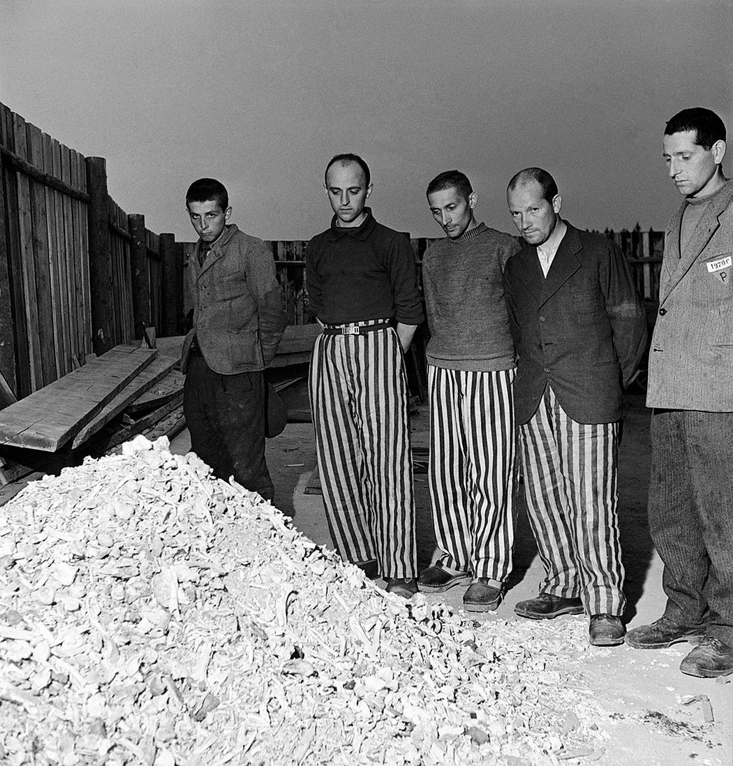 Released prisoners in striped prison dress beside a heap of bones from bodies burned in the crematorium Buchenwald, Germany, 1945 © Lee Miller Archives, England 2020 All rights reserved. leemiller.co.uk