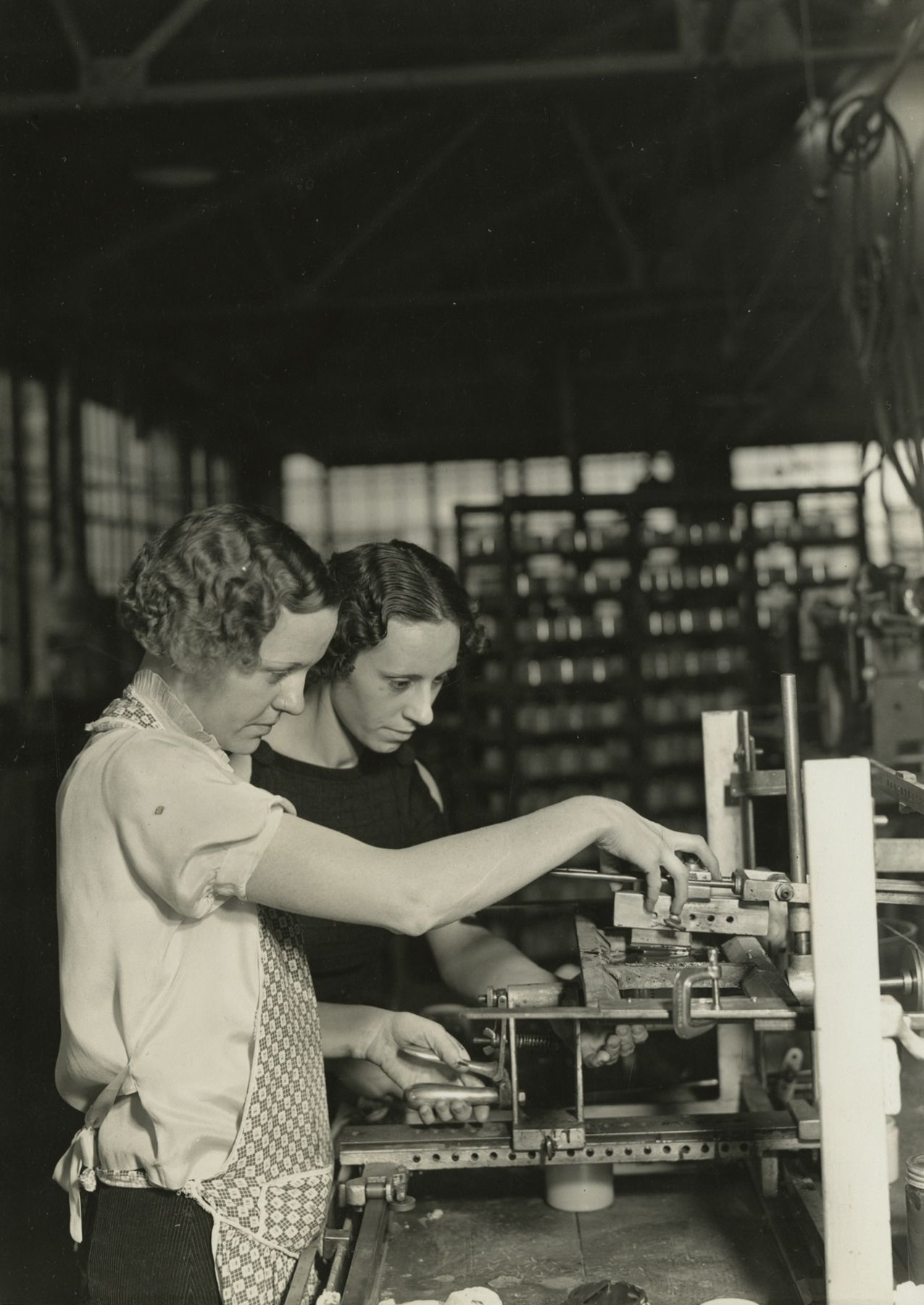 Two girls stamping glass jars in the art room at T. C. Wheaton Company. This is a stamping device developed by this company for lettering painted bottles. Ink is put under the screen in which there are perforations for the lettering, and the jar is rolled over the top of it. The girl in front is controlling the lever which presses the jar as it rolls over the screen. T.C. Wheaton Company, Millville, New Jersey, 1936-37 Gelatin silver print; printed c.1936-37