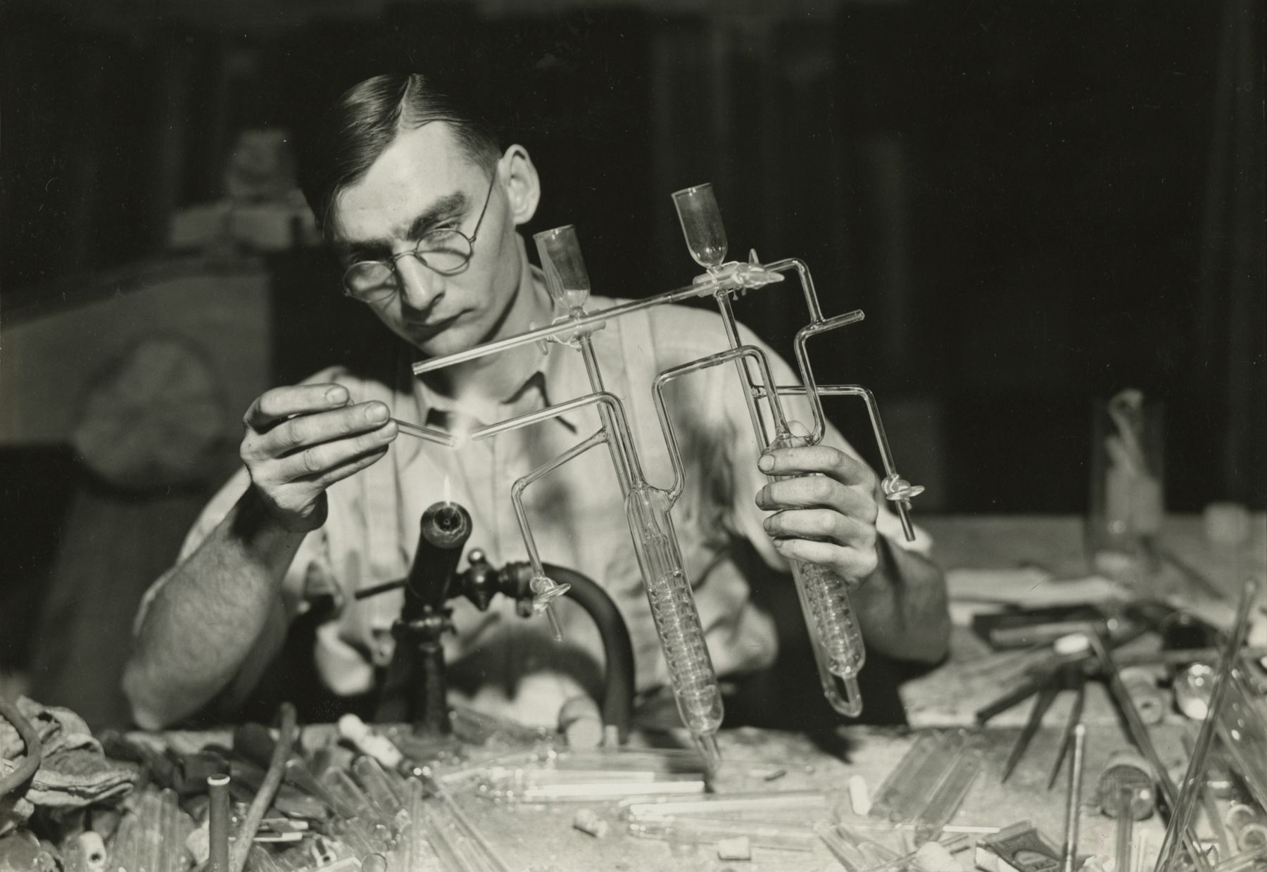 Glass worker finishing the end of a sulphur determinator. Here the worker is smoothing off the end of the tubing after heating it over the glass flame. L.G. Nestor Co., Millville, NJ, March 26, 1937  Gelatin silver print; printed c.1937