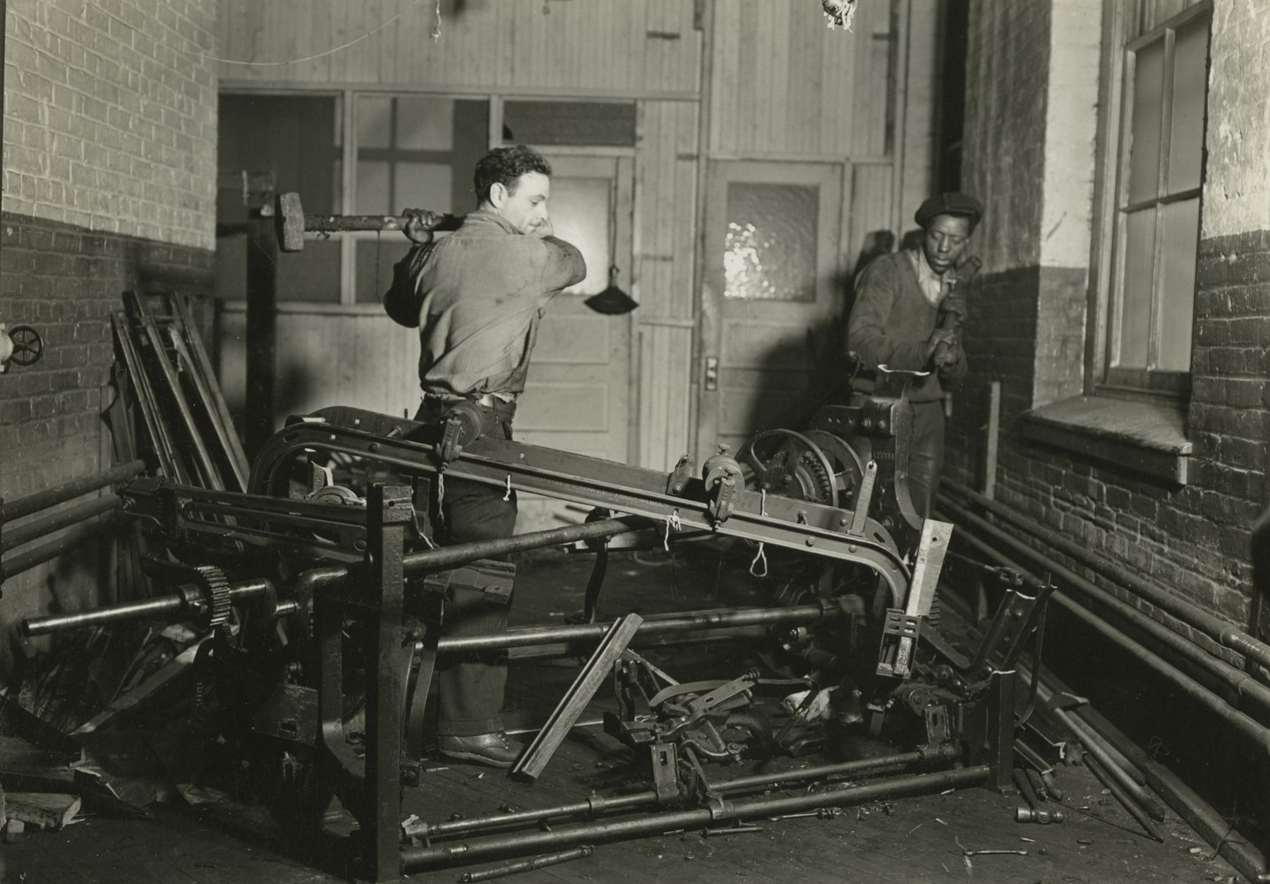 Scrap metal junkies breaking up old looms, to be sold for scrap iron and said to be sent to Japan for munitions, Paterson, New Jersey, 1936